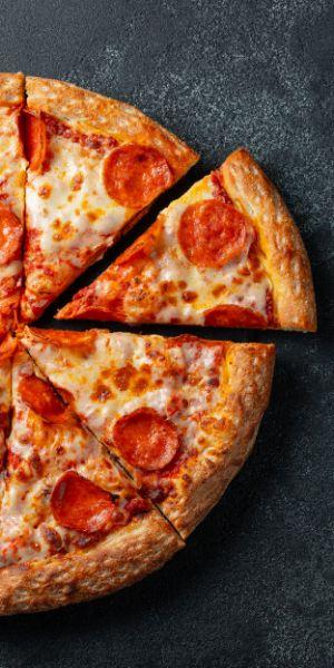 gorąca pizza z serem i salami pocięta na kawałki